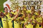 Australian captain Michael Clarke holds the trophy with his teammates as they celebrate their seven wicket win over New Zealand in the Cricket World Cup final in Melbourne, Australia.
