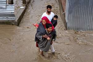 Kashmiri men assist a woman and a child to evacuate from a flooded area in Srinagar.