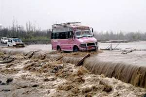 Vehicles pass through submerged bridge in a flooded Larkipora area in Anantnag, south Kashmir.