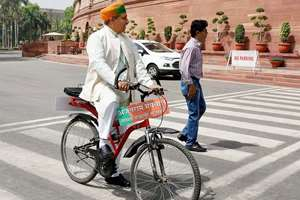 BJP MP Arjunram Meghwal arrives at Parliament on bicycle on the first day of the second part of the Budget session, in New Delhi.