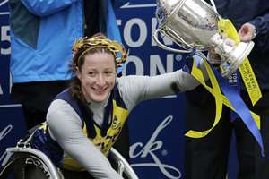 Tatyana McFadden, of Russia, hoists her trophy after winning the women's wheelchair division of the Boston Marathon, in Boston.