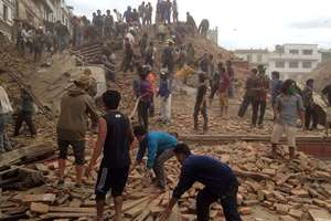 Volunteers help with rescue work at the site of a building that collapsed after an earthquake in Kathmandu, Nepal.