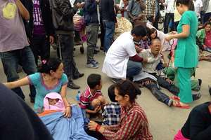 An injured man receives treatment outside the Medicare Hospital in Kathmandu, Nepal.