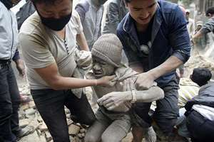 A man being rescued after a massive earthquake, in Nepal.