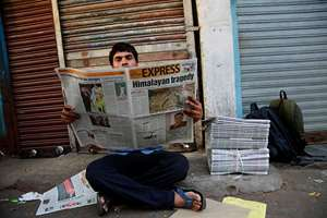 An Indian man reads a newspaper with front-page news of Nepal earthquake  in Mumbai.