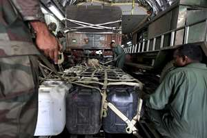 Plastic containers with drinking water is loaded into an Indian Air Force aircraft headed to Nepal, at an Indian Air Force base near New Delhi,