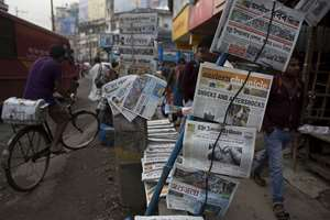 Indian newspapers with front-page news of Nepal earthquake are displayed for sale on a pavement in Gauhati.
