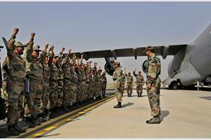 Indian soldiers on rescue mission to Nepal shout patriotic slogans before boarding an Indian Air Force aircraft near New Delhi