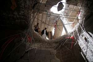 Yemeni men look through a hole in a building damaged by a recent Saudi-led airstrike which hit a site which many believe was a large weapons cache in Yemen's capital, Sanaa.  With combatants fighting in neighborhoods and Saudi-led coalition warplanes pounding Iran-backed rebels from the sky,