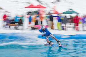 A snowboarder participates in a water sliding contest, in which athletes are gliding over a pool embedded in snow, in Verbier, southwestern Switzerland.