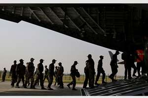 Indian soldiers on rescue mission to Nepal, board an Indian Air Force aircraft near New Delhi