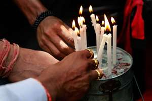 Dabbawalas light candles on a tiffin box for the victims of Nepal's earthquake, outside a railway station in Mumbai.
