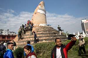 A man takes a selfie at the historic Dharahara Tower, a city landmark, that was damaged in Saturday's earthquake in Kathmandu, Nepal.