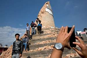 Locals take snapshots with their cell phones at the historic Dharahara Tower, a city landmark, that was damaged in the earthquake in Kathmandu, Nepal.