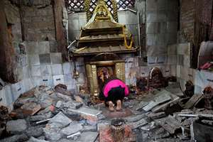 A woman offers prayers at Indrayani temple, that was damaged in the earthquake, in Kathmandu, Nepal.