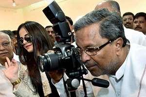 Karnataka CM Siddaramaiah with actress Jeniffer Kothwal, tries his hand on camera during the inauguration of