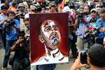 A team lawyer for two Australians Myuran Sukumaran and Andrew Chan carries a self-portrait drawn by Sukumaran after visiting the prison island of Nusakambangan at Wijayapura port in Cilacap, Central Java, Indonesia.