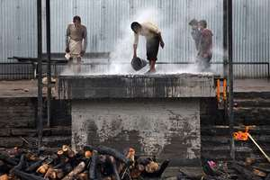 A cremation ground worker pours water to cool the ash after the cremation of a victim of earthquake, at the Pashupatinath temple on the banks of Bagmati river in Kathmandu, Nepal.
