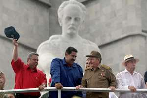 Back-dropped by a statue of Cuba's independence hero Jose Marti Cuban President Raul Castro (center right) talks with Venezuelan President Nicolas Maduro as they watch the May Day parade at Revolution Square, in Havana, Cuba. Thousands of people converged on the plaza despite the rain for the traditional march. Also pictured are Workers' Union chief Ulises Guilarte (left) and First Vice President of the Council of State Jose Ramon Machado Ventura (right).