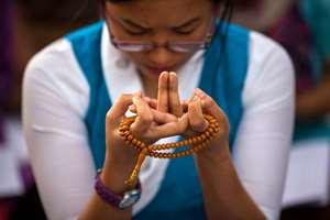 An exile Tibetan woman prays on the occasion of the Buddha Jayanti festival, in New Delhi.