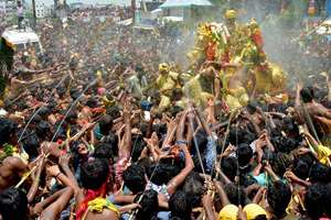Devotees perform holy bath of the idol of Lord Kallazhagar in the Vaigai river in Madurai on the last day of Chithrai festival.