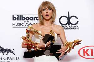 "Taylor Swift poses in the press room with the awards for top Billboard 200 album for ""1989,"