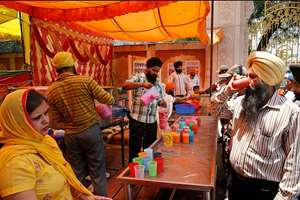 Sikhs distribute flavored milk to passersby to mark the martyrdom of Guru Arjan Dev in New Delhi.