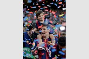 FC Barcelona's Lionel Messi celebrates with his son after winning the Spanish League title, at the end of their Spanish La Liga last round soccer match against Deportivo Coruna at the Camp Nou stadium in Barcelona, Spain.