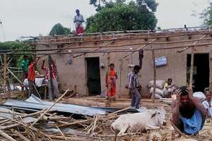 A man sitting in front of a wrecked house following a cyclonic storm at Amritapur village in South Dinajpur district of West Bengal