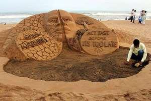 Sand artist Sudarsan Pattnaik creates a sand sculpture on Global warming at Puri beach, of Odisha.