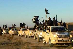 Militants of the Islamic State group hold up their weapons and wave its flags on their vehicles in a convoy on a road leading to Iraq, while riding in Raqqa city in Syria.