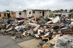 Damaged homes stand next to others that were razed when a powerful tornado touched down in Ciudad Acuna, northern Mexico. The tornado raged through the city on the U.S.-Mexico border, destroying homes and flinging cars like matchsticks. At least 13 people were killed.