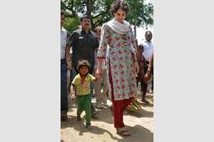 Priyanka Vadra walks with a kid during her visit to Raebareli in Uttar Pradesh.