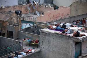 Men sleep on the roofs of houses to beat the heat, in New Delhi.