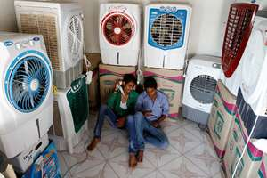 Salesboys sit in a shop selling air coolers on a hot summer day in Ahmedabad.