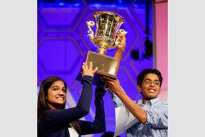 Vanya Shivashankar, 13, left, of Olathe and Gokul Venkatachalam, 14, of St. Louis, hold up the trophy as co-champions after winning the finals of the Scripps National Spelling Bee in Oxon Hill, Madison, USA.