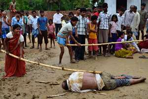 A man and a woman strike the body of a school director with sticks as it lies on the ground in Nirpur village, about 90 kilometers southeast of Patna, in Bihar. Police are investigating the mob killing of the school director after two of the school's students aged 10 and 11, were discovered dead in a nearby pond.