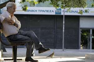 With the Greek cabinet deciding that banks would remain shut for six business days and restrictions would be imposed on cash withdrawals, an elderly man waits outside a closed bank in Athens, Greece.