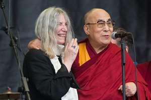 The Dalai Lama speaks to the crowd during singer Patti Smith's, left, performance at the Glastonbury music festival at Worthy Farm, Glastonbury, England.