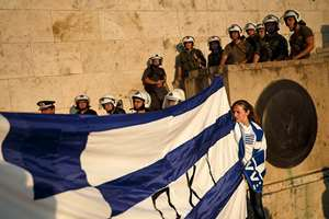 Supporters of the NO vote in the upcoming referendum hold a Greek flag as riot police block the entrance of the parliament during a rally at Syntagma square, in Athens.
