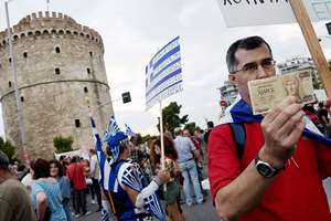Supporter of the NO vote in the upcoming referendum, holds an old 1,000 drachma bank note during a rally in the northern Greek port city of Thessaloniki. Anxious Greek pensioners swarmed closed bank branches and long lines snaked at ATMs as Greeks endured the first day of serious controls on their daily economic lives ahead of a July 5 referendum that could determine whether the country has to ditch the euro currency and return to the drachma.