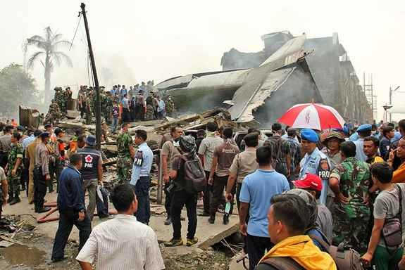Military personnel inspect the wreckage of an Air Force cargo plane that crashed in Medan, North Sumatra, Indonesia.
