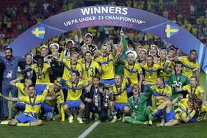 Sweden's team celebrates with the trophy under the winner board after winning the Euro U21 soccer championship final match between Sweden and Portugal, at the Eden stadium in Prague, Czech Republic. Sweden defeated Portugal on penalties with 4-3.