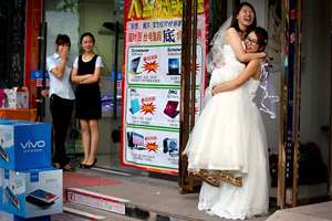 Li Tingting, second from right, laughs as she is lifted off the ground by her wife Teresa Xu, right, outside of a beauty salon where the two were preparing for their wedding as clerks from an adjacent shop look on in Beijing. A prominent Chinese lesbian couple held a simple ceremony to announce their informal marriage, in their latest effort to push for legalisation of same-sex unions in China.
