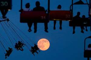 The moon rises as people sit on rides at the State Fair Meadowlands, in East Rutherford, New Jersey.