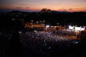Demonstrators gather during a rally organised by supporters of the Yes vote as the ancient Acropolis hill is seen in the background in Athens.