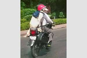 A man with his pet, wearing helmet, riding a motorcycle, in New Delhi.