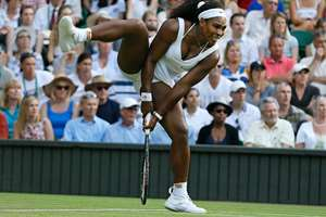 Serena Williams of the United States raises her leg as she reacts as she plays Heather Watson of Britain during their singles match at the All England Lawn Tennis Championships in Wimbledon, London.