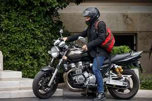 Greek Finance Minister Yanis Varoufakis sits on his motorbike as he leaves Maximos Mansion in Athens. Varoufakis has resigned saying he was told shortly after the Greek referendum result that the some eurozone finance ministers and Greece's other creditors would prefer he not attend the ministers' meetings.