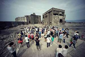 """In this June 29, 2015 photo, tourists visit a part of Hashima Island, commonly known as Gunkanjima, which means """"Battleship Island,"""" off Nagasaki, Nagasaki Prefecture, southern Japan. The UN's cultural body conferred world heritage status on a number of new sites including some seen as representative of Japan's industrial revolution, as South Korea lifted its opposition to the listing. UNESCO's World Heritage committee added 23 sites considered representative of Japan's industrial revolution under Emperor Meiji (1868-1910) to its vaunted list, at a meeting taking place in the western German city of Bonn until July 8."""